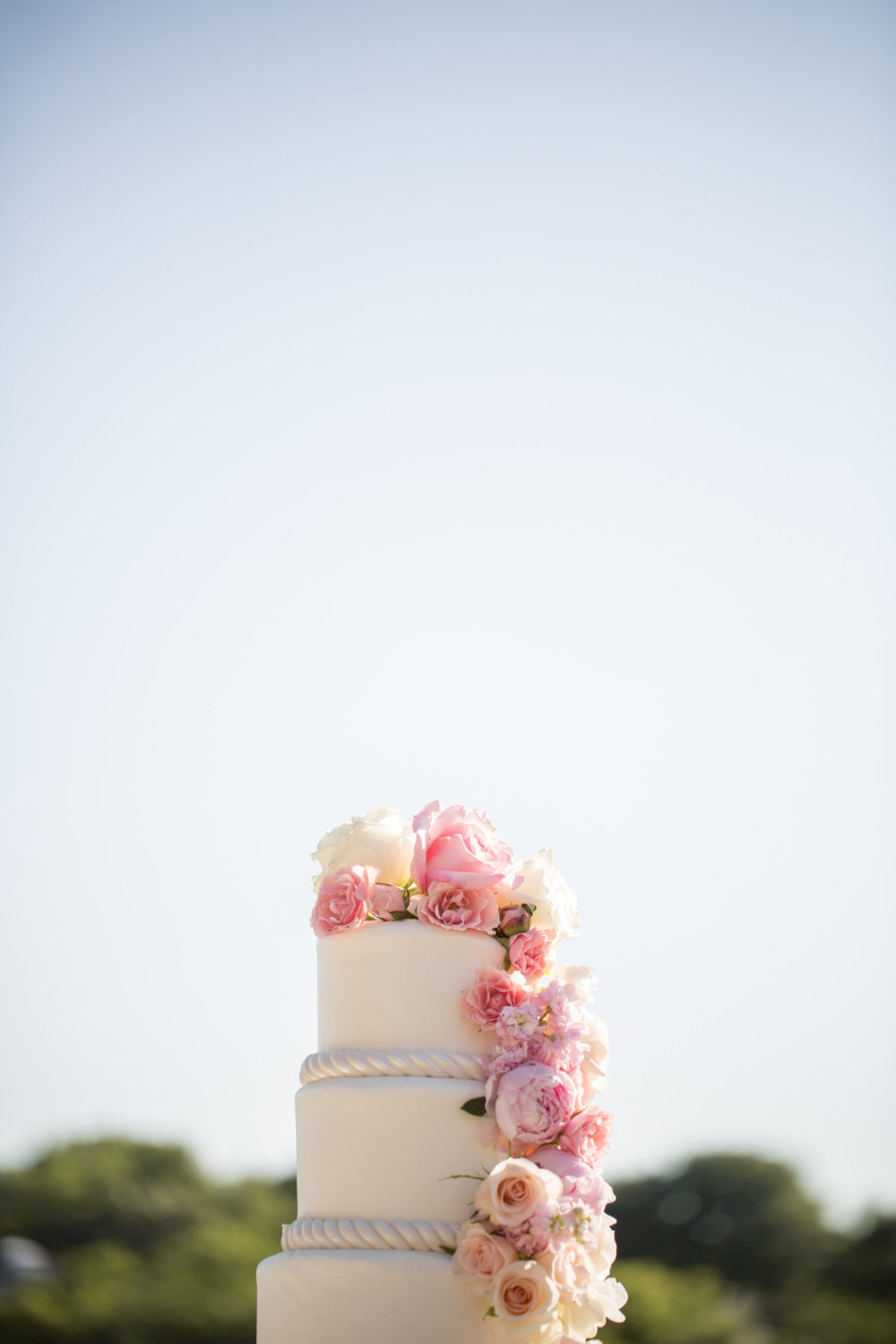 custom wedding cake with cascading blush florals