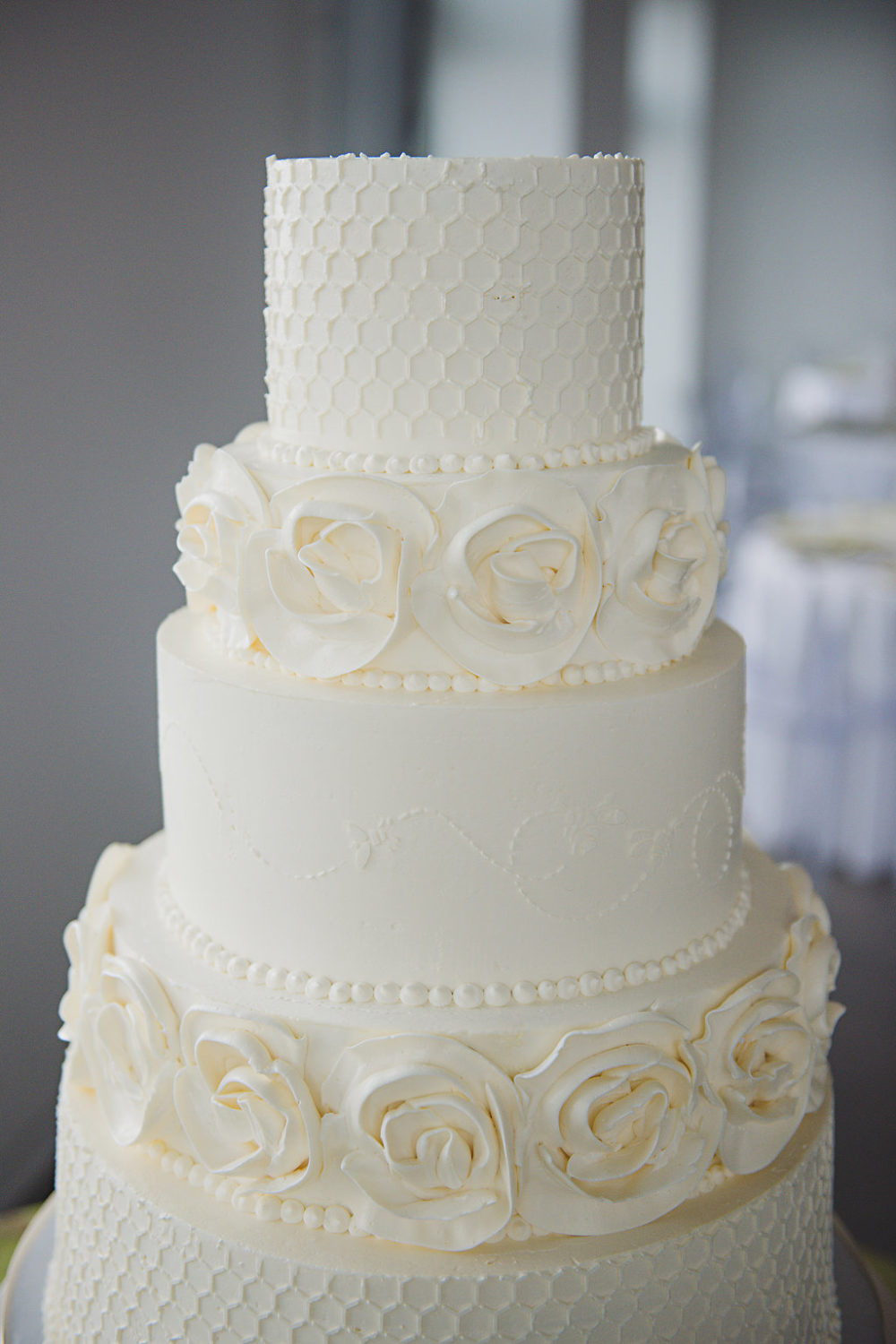 white wedding cake, honey combs and roses